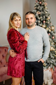 Casal jovem feliz abraçando, acariciando, celebrando as férias de inverno juntos perto da árvore de natal decorada na sala de estar.