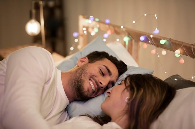 Casal jovem feliz, abraçando na cama