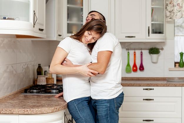 Casal jovem feliz, abraçando na cozinha