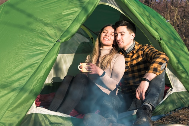 Casal jovem feliz, acampar ao ar livre, sentado na barraca e apreciar o pôr do sol
