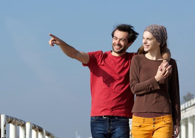 Casal jovem feliz andando ao ar livre e apontando