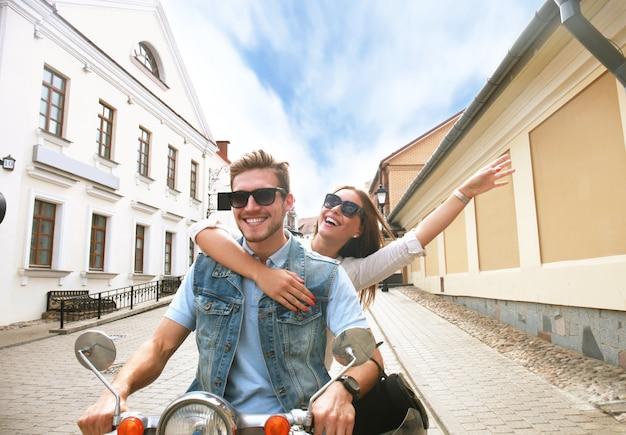 Casal jovem feliz andando de scooter na cidade. um cara bonito e uma jovem mulher viajam. conceito de aventura e férias.