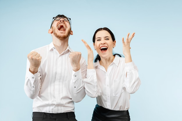 Casal jovem feliz animado com prazer. empresário e mulher isolados na parede azul