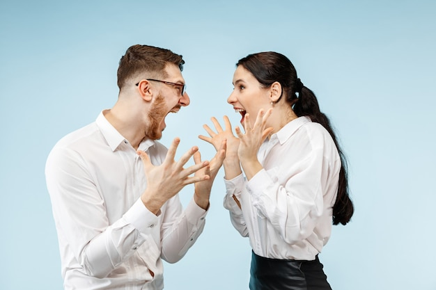 Casal jovem feliz animado, olhando para a câmera com prazer. empresário e mulher isolados no fundo azul do estúdio