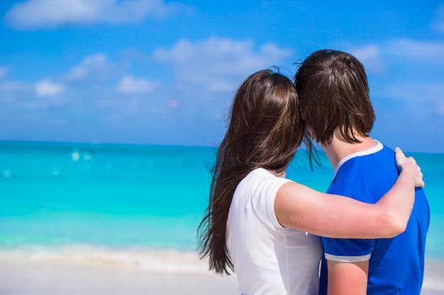 Casal jovem feliz, aproveitando as férias de verão na praia tropical