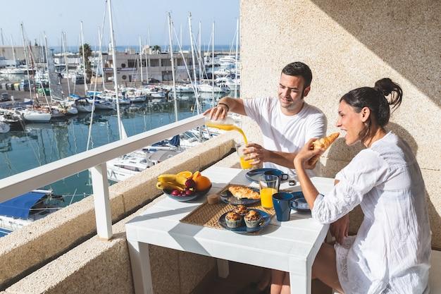 Casal jovem feliz, aproveitando o café da manhã no terraço