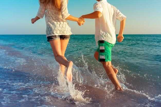 Casal jovem feliz, aproveitando o mar