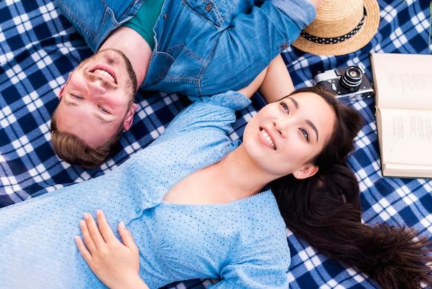 Casal jovem feliz, aproveitando o resto no cobertor