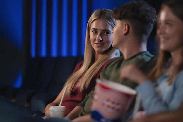 Casal jovem feliz assistindo filme no cinema, conversando.