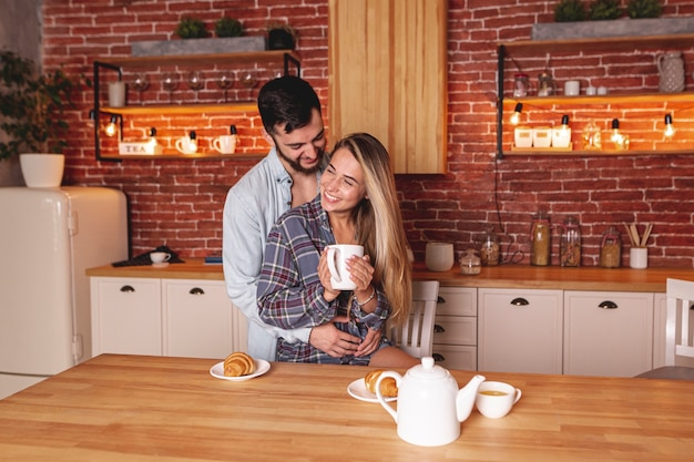 Casal jovem feliz, bebendo chá na cozinha