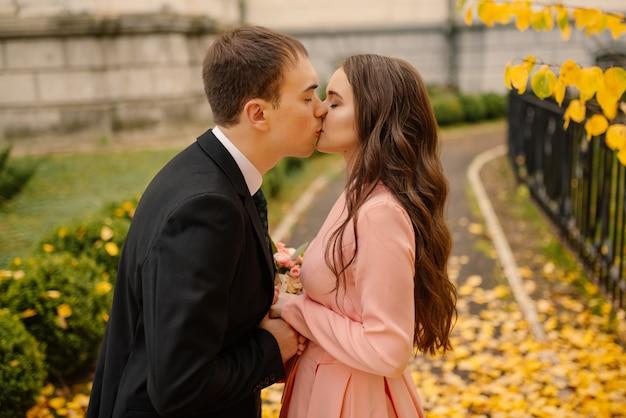 Casal jovem feliz casamento recém-casado na caminhada no parque outono dourado amarelo outono perto da catedral gótica de atmosfera vintage.
