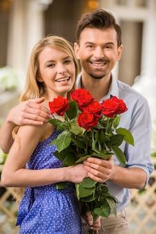 Casal jovem feliz com buquê de rosas em uma data.