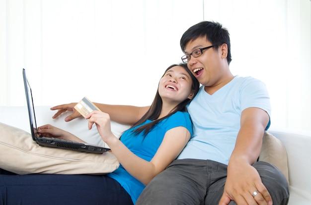 Casal jovem feliz com cartão de crédito e laptop
