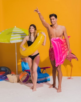 Casal jovem feliz com círculo de natação e colchão na praia