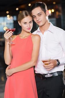 Casal jovem feliz com cocktails no partido