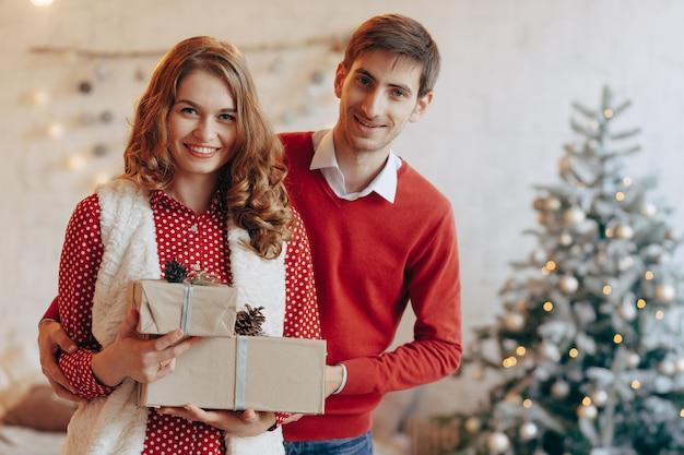 Casal jovem feliz com presentes de natal