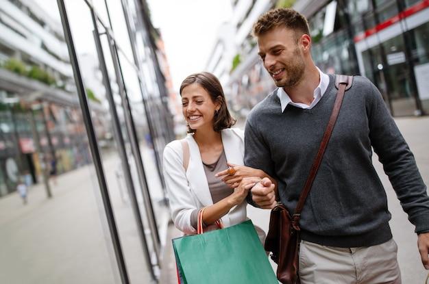 Casal jovem feliz com sacolas de compras. venda, viagens, amor conceito de consumismo e pessoas.