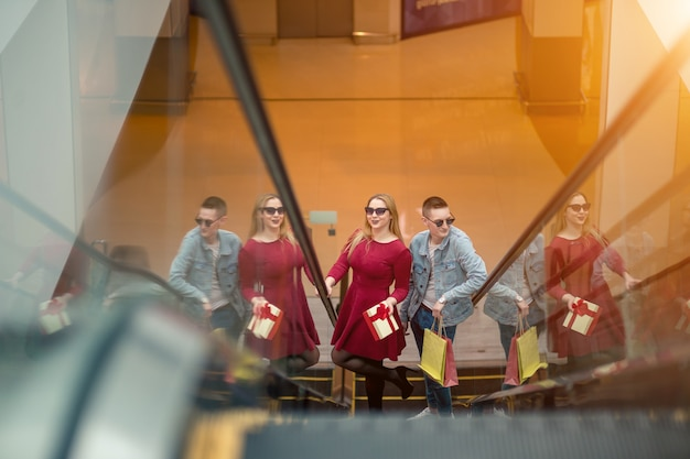 Casal jovem feliz com sacos de compras descendo pela escada rolante e apontando o dedo no shopping