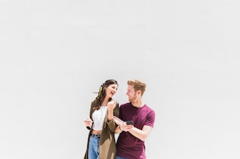 Casal jovem feliz com smartphone em pé contra um fundo branco