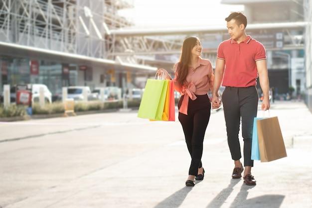 Casal jovem feliz de compradores andando na rua comercial em direção às compras de black friday