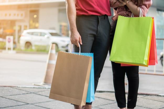 Casal jovem feliz de compradores andando na rua comercial em direção e segurando sacolas coloridas na mão.