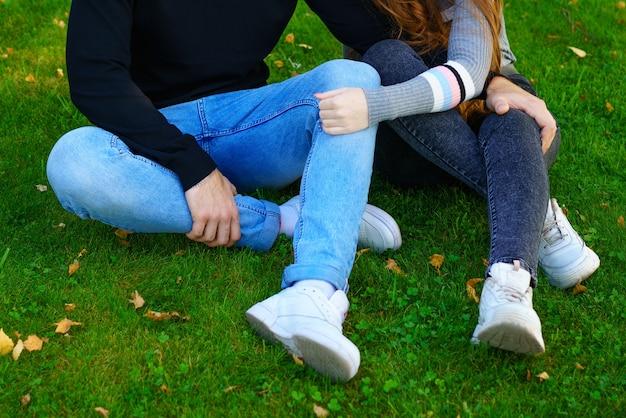 Casal jovem feliz de etnia caucasiana, homem e mulher em roupas casuais, sentado abraçando no p ...