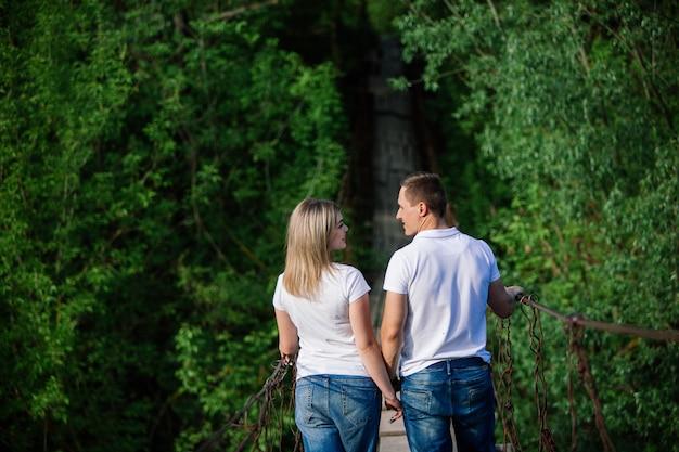 Casal jovem feliz, de mãos dadas em uma ponte de madeira. casal jovem feliz, se divertindo ao ar livre juntos. totalmente apaixonado. casal apaixonado, olhando um ao outro e sorrindo. data romântica no parque verde
