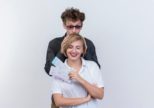 Casal jovem feliz de turistas, homem e mulher com passagens aéreas, se divertindo juntos em pé sobre uma parede branca