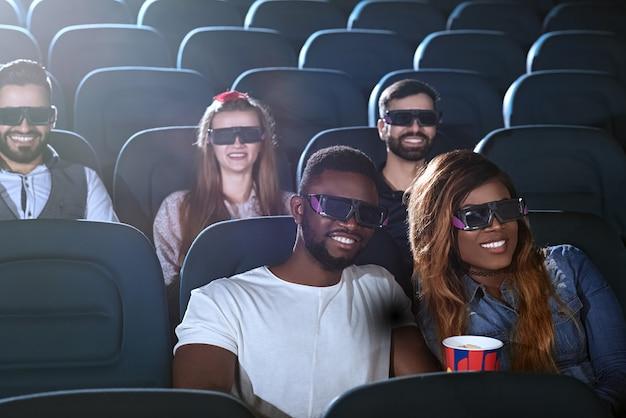 Casal jovem feliz, desfrutando de um encontro no cinema sorrindo alegremente usando óculos 3d