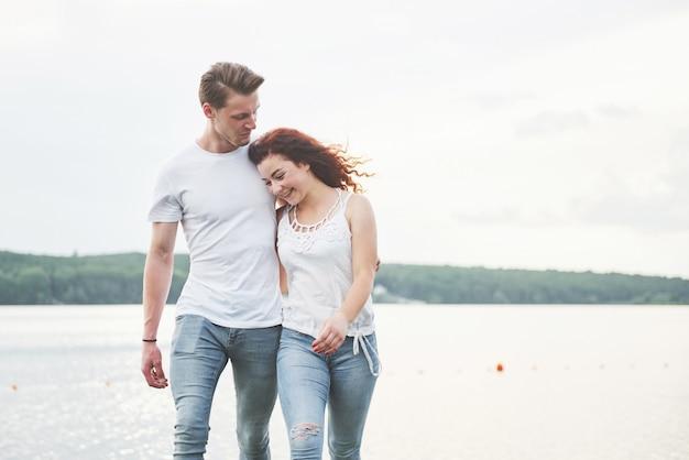 Casal jovem feliz, desfrutando de uma praia solitária