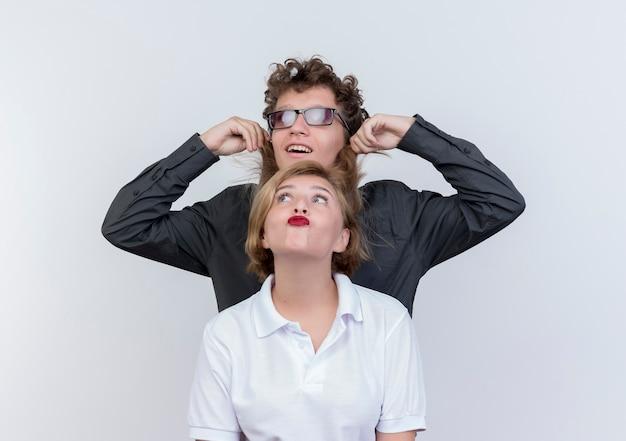 Casal jovem feliz e mulher se divertindo juntos em pé sobre uma parede branca