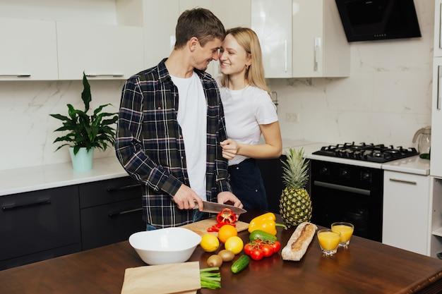 Casal jovem feliz e positivo está cortando a salada de legumes.