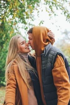 Casal jovem feliz em amigos de adolescentes amor vestidos em estilo casual, beijando na rua da cidade na estação fria