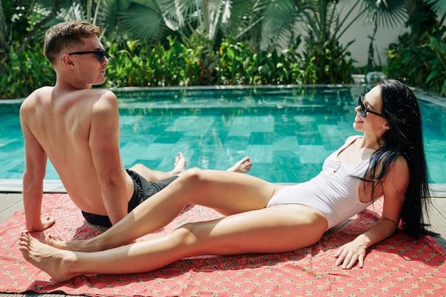 Casal jovem feliz em forma bonita, descansando, nadando, tomando banho de sol no cobertor e conversando