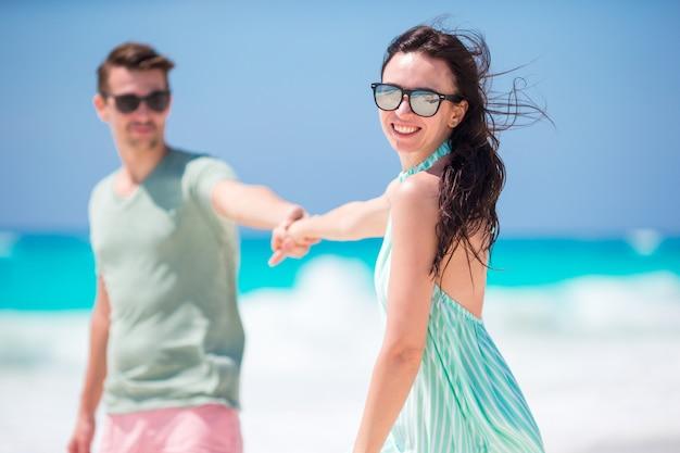 Casal jovem feliz em lua de mel na praia desfruta de férias românticas