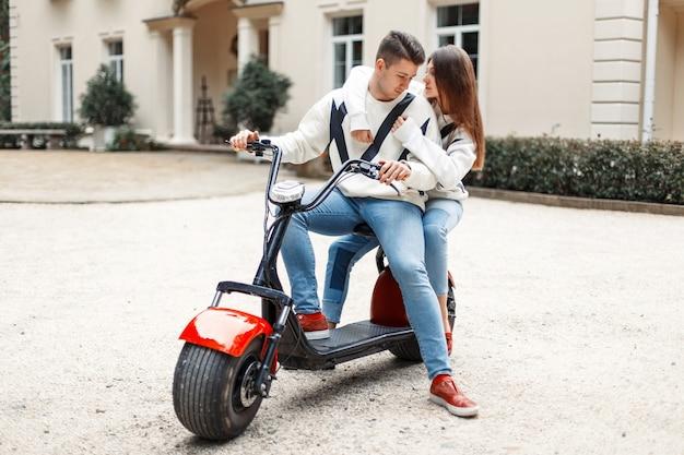 Casal jovem feliz em roupas da moda elegantes anda em uma bicicleta elétrica perto do hotel