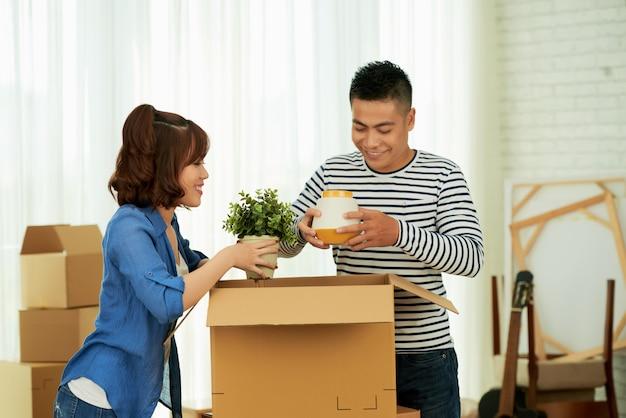 Casal jovem feliz, embalando as coisas para a mudança para a nova casa