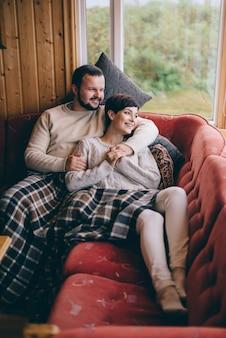 Casal jovem feliz encontra-se em um sofá em uma casa de campo.