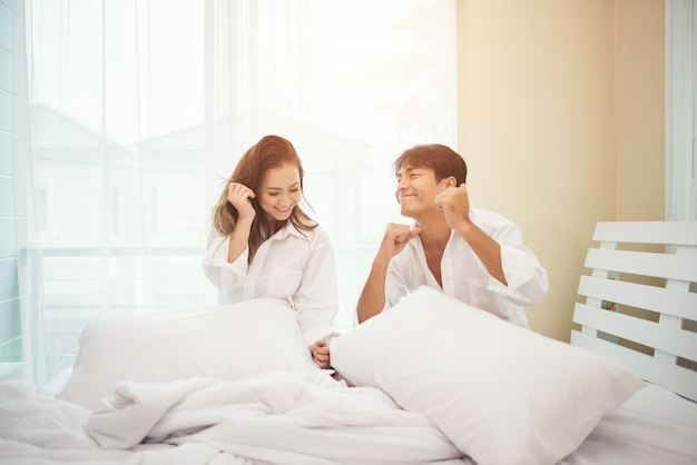 Casal jovem feliz está se divertindo na cama