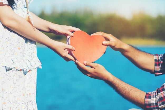 Casal jovem feliz está segurando corações de papel vermelho