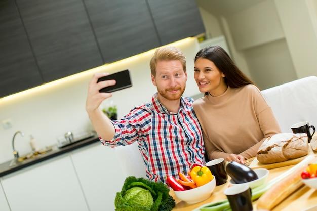 Casal jovem feliz fazendo selfie enquanto cozinhava comida na cozinha