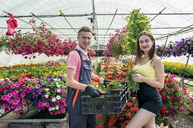 Casal jovem feliz florista cuidar das flores em uma estufa. negócios de família
