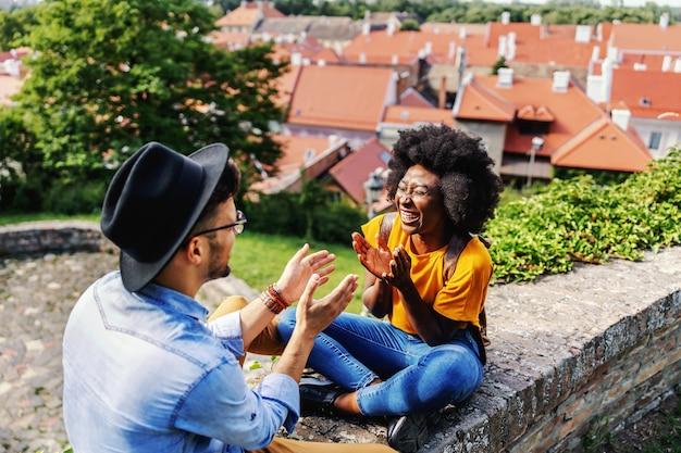 Casal jovem feliz hippie sentado ao ar livre em uma parte velha da cidade, sorrindo e flertando.
