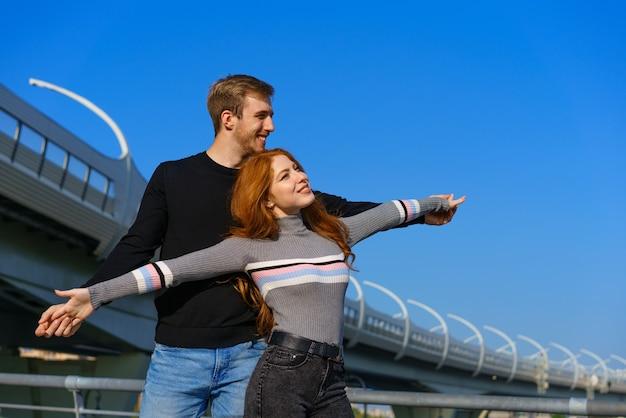 Casal jovem feliz, homem e mulher com longos cabelos vermelhos em pé no contexto de um céu azul e uma ponte em roupas casuais