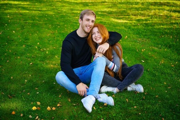 Casal jovem feliz, homem e mulher em roupas casuais, sentados abraçando no parque na grama verde em um dia ensolarado