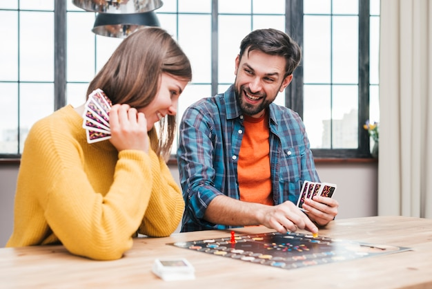 Casal jovem feliz jogando o jogo de tabuleiro na mesa de madeira
