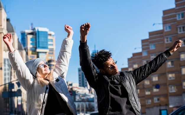 Casal jovem feliz, levantando as mãos dançando contra edifícios