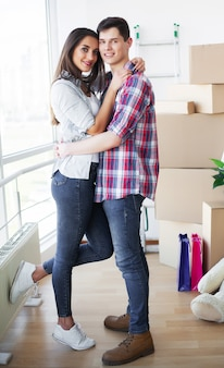 Casal jovem feliz, movendo-se juntos no novo apartamento