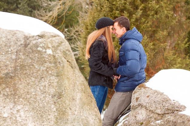Casal jovem feliz nas montanhas de inverno