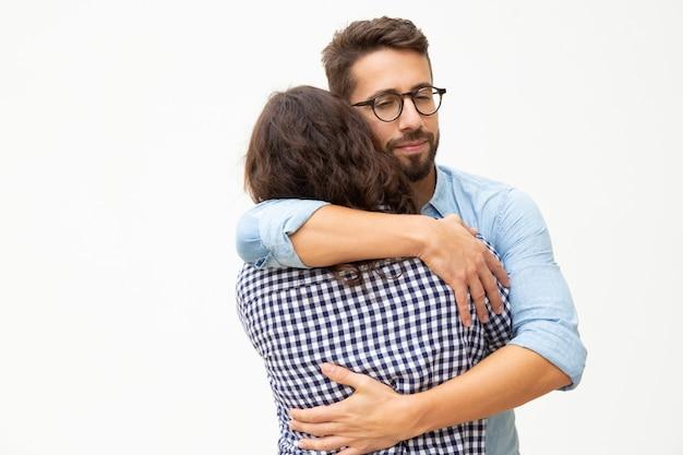 Casal jovem feliz no amor abraçando
